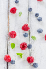 Raspberries and blueberries on white wooden background
