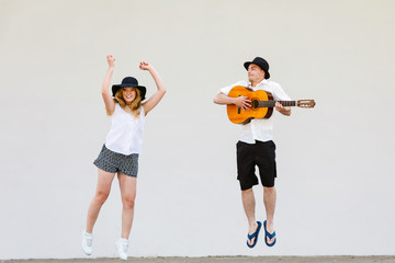 Man with guitar and woman jumping
