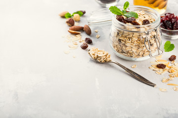 Oat flakes in glass jar with honey, raisins and nuts. Healthy breakfast concept with copy space.