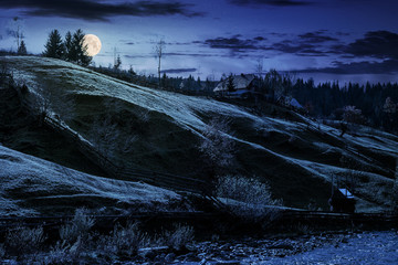 grassy rural hillside near the village at night in full moon light. beautiful countryside scenery in autumn