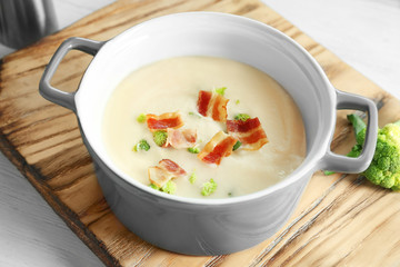 Saucepan of yummy potato soup with bacon on wooden board