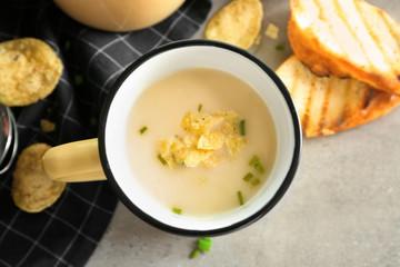 Mug of yummy potato soup with crisps on table