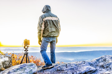 Standing young man photographer with camera and tripod on cold autumn morning in jacket in Bear Rocks, West Virginia taking pictures of sunrise