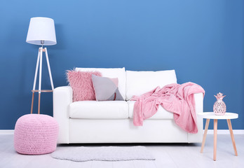 Comfortable sofa on color wall background