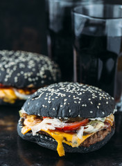 Black burger with meat, cheddar cheese and vegetables. Rustic style