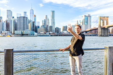 Young hipster man standing taking selfie picture by fence in Brooklyn Bridge Park overlooking the NYC New York City Manhattan cityscape skyline with water bay during sunset