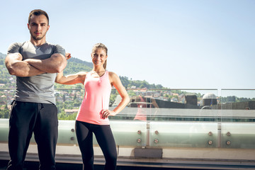 Two young adult fitness models posing on rooftop.