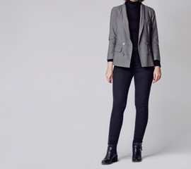 Woman wearing stylish and smart outfit with black turtleneck, gray elegant double-breasted blazer, black skinny jeans and black ankle boots isolated on gray background. Copy space