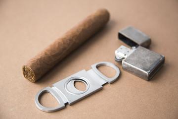 Cigar, Cigar Cutter and Metal Lighter on Dark Background Natural Light Selective Focus