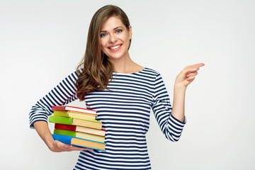 student girl holding pile of books and pointig with finger