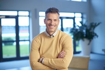 Confident mature businessman smiling to you