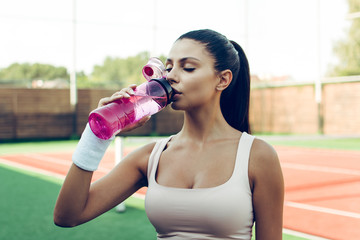 Sip of fresh water. Beautiful young woman holding drinking water while standing on the tennis court