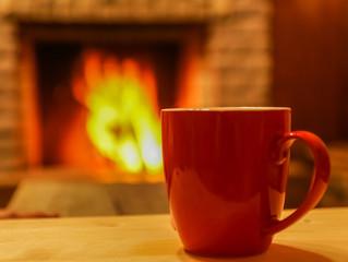 Mug  of tea, on wooden table, before  cozy fireplace, defocused.