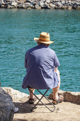 Old man sitting on a bench by the river under the tree on a sunny day