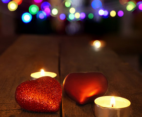 christmas decorations with candles and heart shape, under  blurred background.
