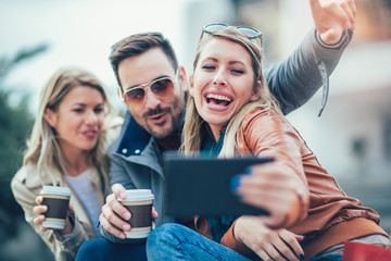 Group of smiling friends taking selfie with digital tablet