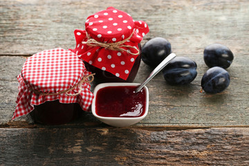 Plum jam in jars with spoon on grey wooden table