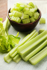 Celery in bowl on white cutting board
