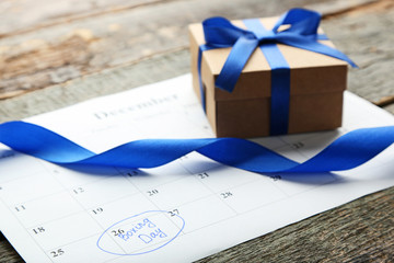 Gift box and calendar list on wooden table. Boxing day concept