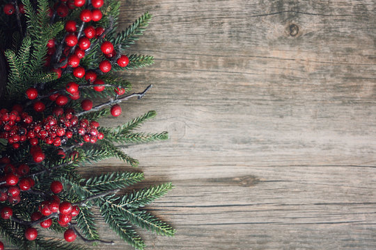 Christmas Evergreen Branches and Berries Over Rustic Wood Background