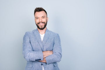 Close up portrait of young successful brunet stock market broker guy on the pure light blue background, he is smiling, wearing smart casual, stands with crossed arms