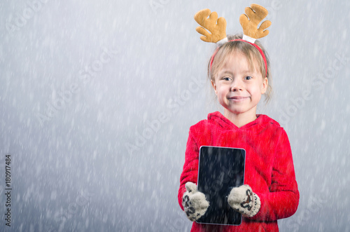 fdea50143 Cute little girl in a red sweater and horns of a deer on a gray ...