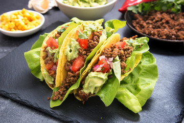 mexican taco corn shells stuffed with fried ground beef, tomato salsa and guacamole on a dark slate plate