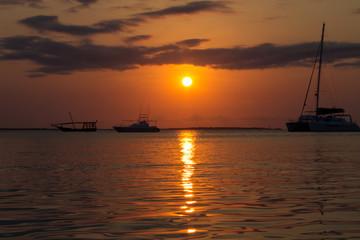 Закат солнца над водой и силуэты яхт и лодок