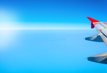 Aviation background with a blue sky and sea landscape. Wing of an airplane with place for your design or signature.