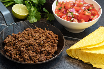 fried ground beef in a pan, as a filling for taco shells with ingredients as tomato salsa, lime and herbs on a dark stone background