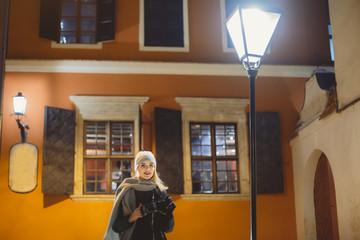 Portrait Beautiful blonde woman walking in european city on a cold winter night