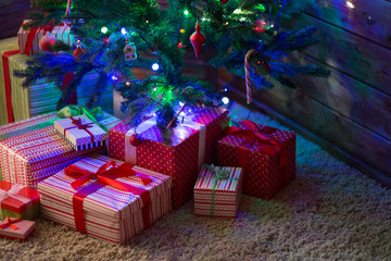 Boxes with gifts for Christmas fir