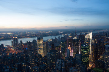 Aerial view of Manhattan New York skyline at sunset, during the blue hours, with lights of skyscrapers turning on.
