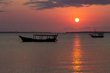 силуэты лодок в океане на фоне янтарного заката солнца