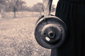 Old metal vintage dumbbell used for heavy weight exercise outside.  Great fitness and workout image.
