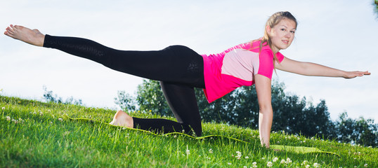 Smiling adult woman in pink T-shirt is practicing yoga
