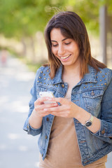 Beautiful Young Ethnic Woman Using Her Smartphone Outside.