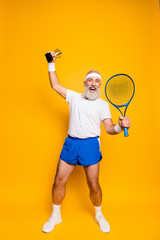 Wow! Competetive best cool healthy modern successful active grandpa with big tennis equipment and reward raised in hand up. Healthcare, weight loss, bodycare, motivation, pride, hobby