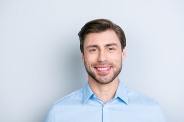 Close up of beaming smile bearded man looking at camera while standing over grey background, he is so stylish
