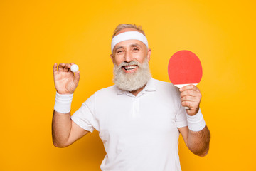 Competetive emotional cool active goofy comic grey haired grandpa with humor grimace and beaming grin, with table tennis equipment. Healthcare, weight loss, bodycare lifestyle