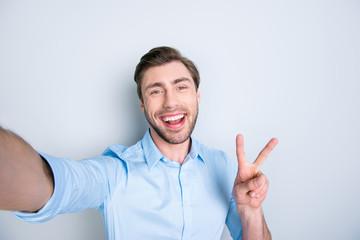 Selfie mania. Close up of confident brunet student  with beaming smile and beard taking a self-portrait  on his mobile phone and showing v-sign while standing over grey background