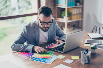 Creative occupation, making decision. Close up of stylish bearded male architect with  mustache in trendy specs and grey formal jacket, choosing the colors for new project, looking at the pantone