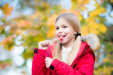 Child girl with long blond ponytail hair eat lollipop