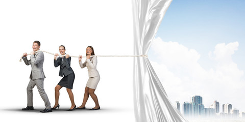 Young businesspeople working in collaboration and pulling white advertisement banner