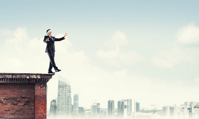 Danger and risk concept with businessman making step from edge