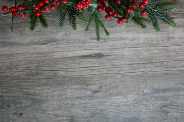 Christmas Pine Tree Branches and Berries Over Rustic Wood Horizontal Background
