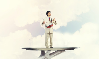 Young businessman on metal tray playing drums against blue sky background