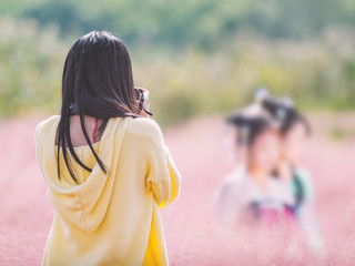 Rear view of a Chinese female photographer taking photos for two girls in beautiful pink hairawn muhly flowers field.
