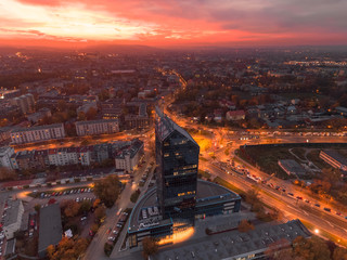 Autocollant pour porte Cracovie Modern architecture office building, Transportation, rush hour traffic, cars on highway interchange in city center. Sunset time, orange and gold light skyline. Drone aerial view of Krakow, Poland.