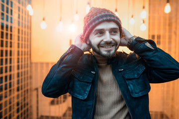 Happy hipster guy against the background of lamps. Holds his hands to the hat.